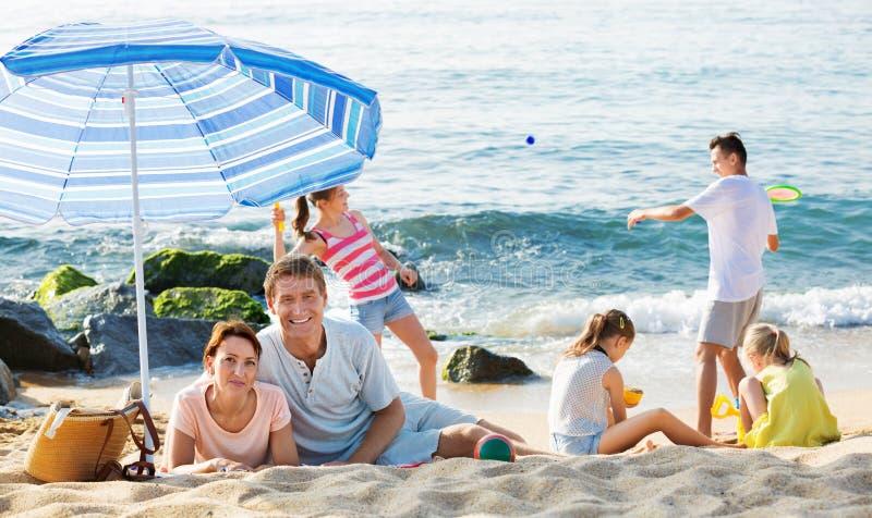 结合放松在海滩,当他们的打活跃的游戏时的孩子 库存照片