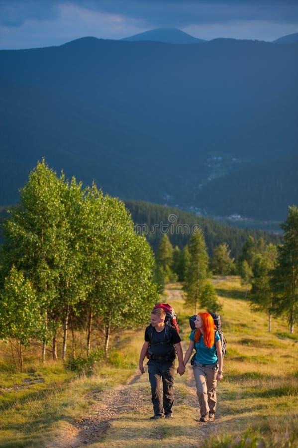 结合有握手的背包的远足者,走在山 免版税库存照片