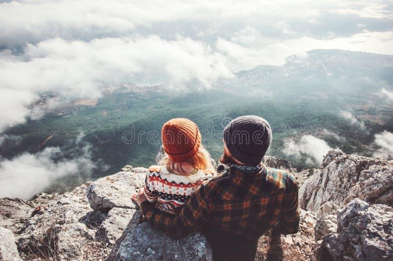 结合男人和妇女坐的拥抱在峭壁 免版税库存图片