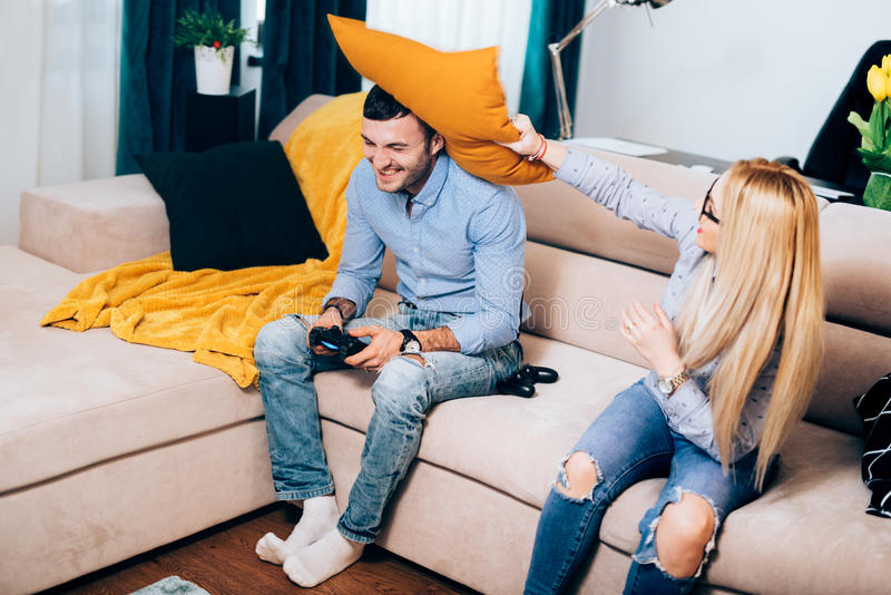 结合获得乐趣在公寓,参与枕头战有吸引力的夫妇在网络游戏争执期间 库存照片