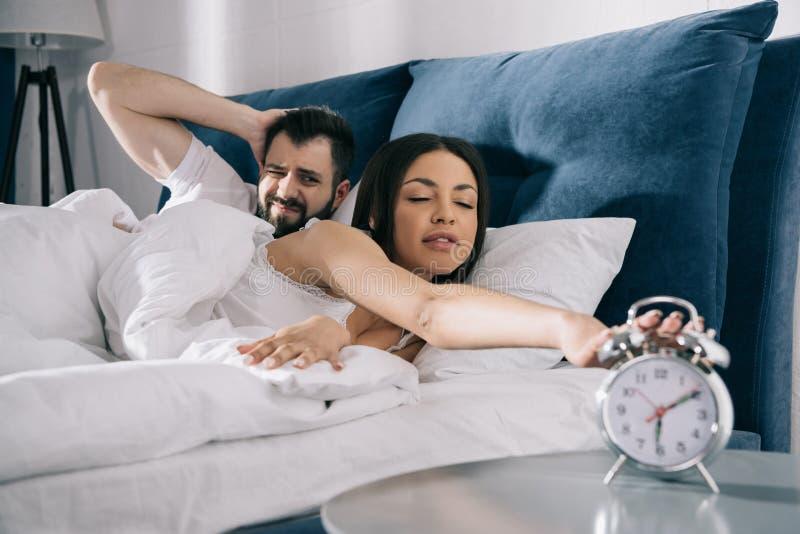 结合设法关闭闹钟,当睡觉在床上时 免版税图库摄影
