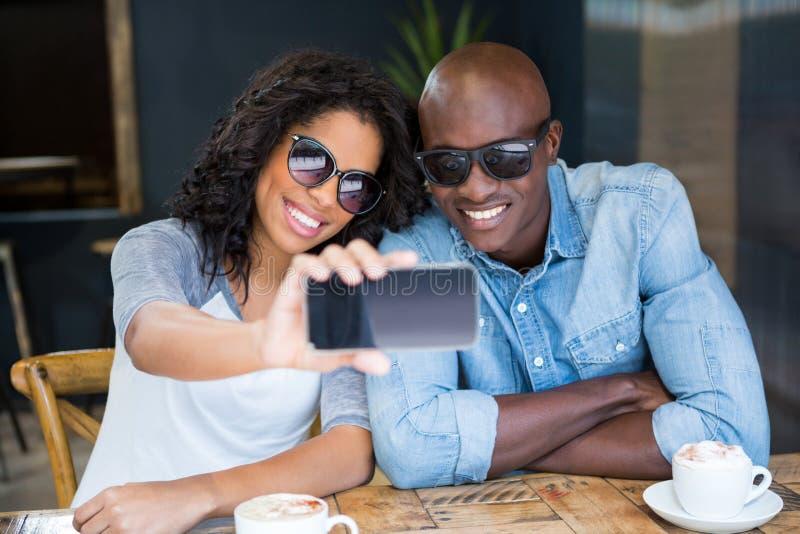 结合采取与巧妙的电话的selfie在咖啡店 免版税库存照片