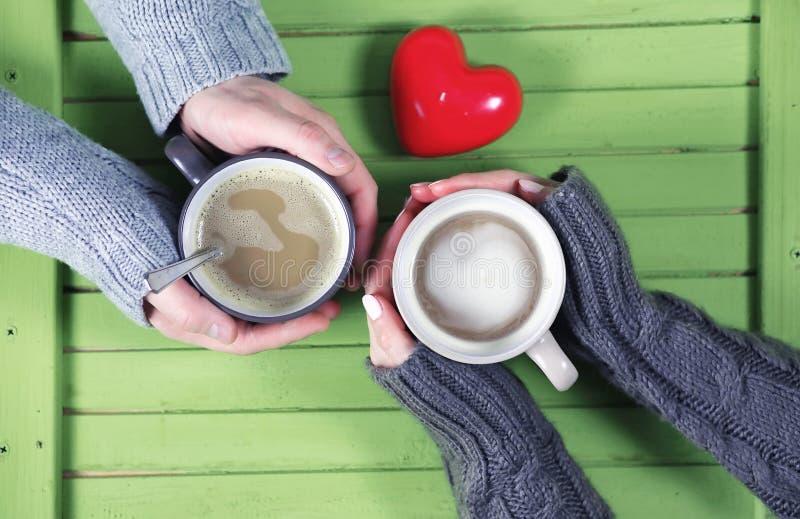 结合饮用的热的咖啡在木桌上在日期 免版税库存照片
