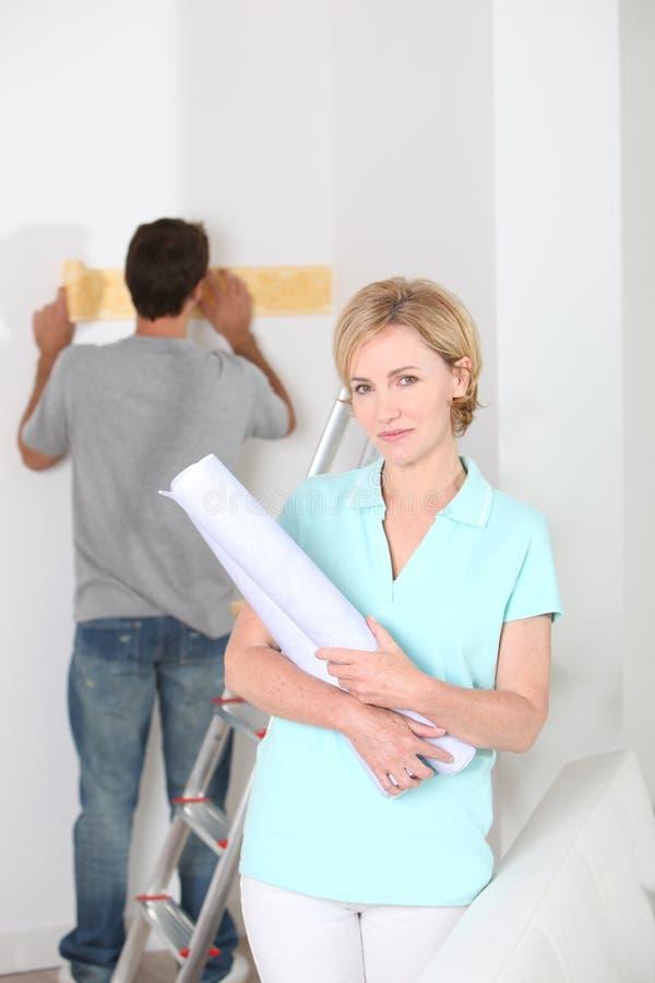 有墙纸卷的妇女 免版税库存照片
