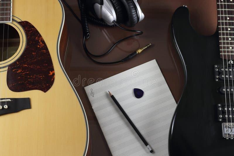 吉他、演播室耳机和音乐叶子 库存照片
