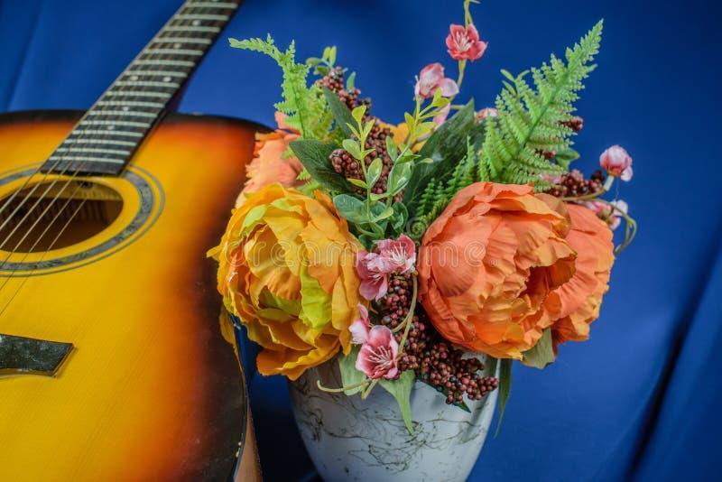 吉他和花在蓝色背景 免版税库存照片