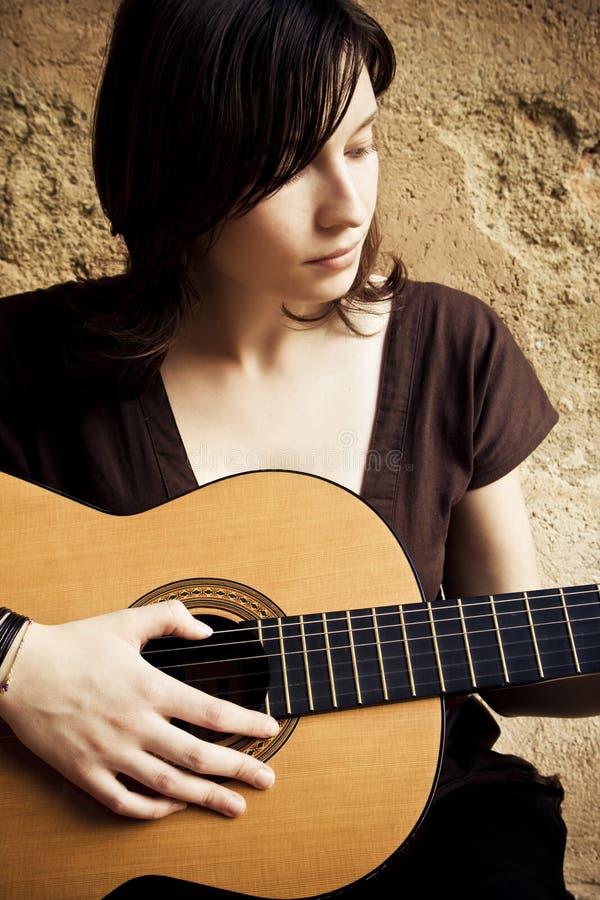 吉他妇女年轻人 免版税库存照片