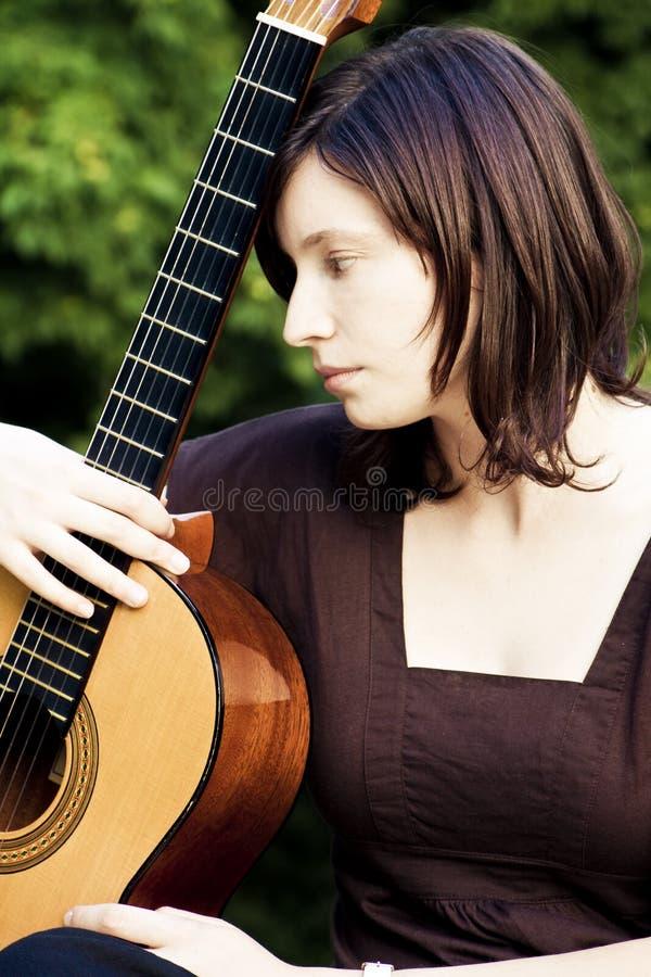 吉他妇女年轻人 免版税库存图片