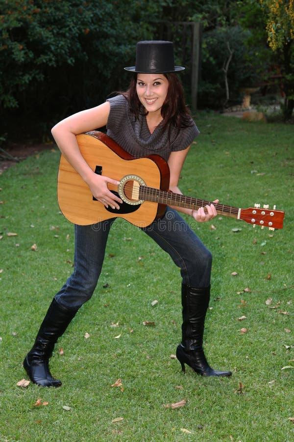 吉他室外俏丽的妇女 免版税库存照片