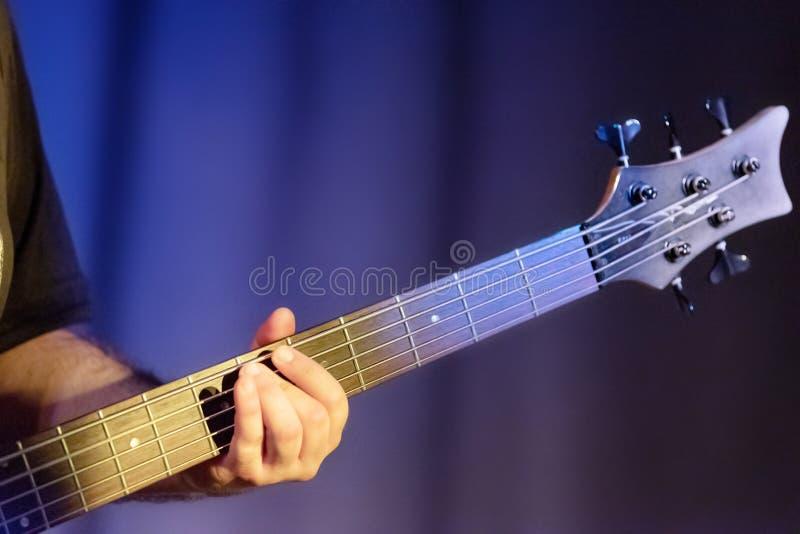 吉他弹奏者使用低音吉他,关闭  免版税库存图片