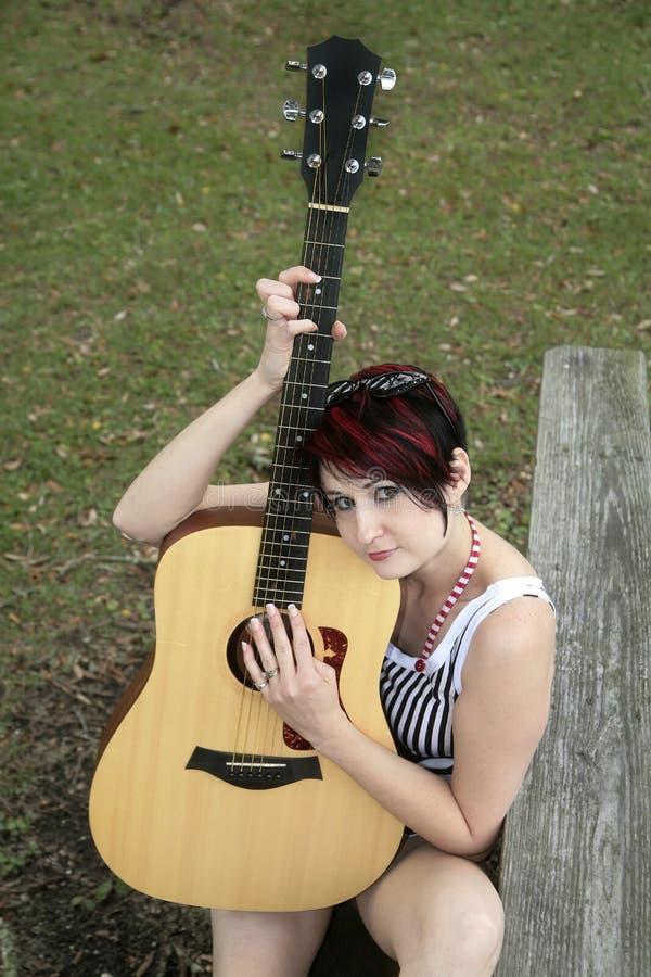 吉他弹奏者公园妇女 图库摄影