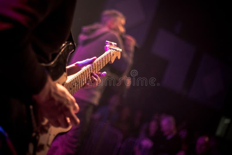 吉他弹奏者在背景中弹在阶段的一把电吉他与光 关闭 图库摄影