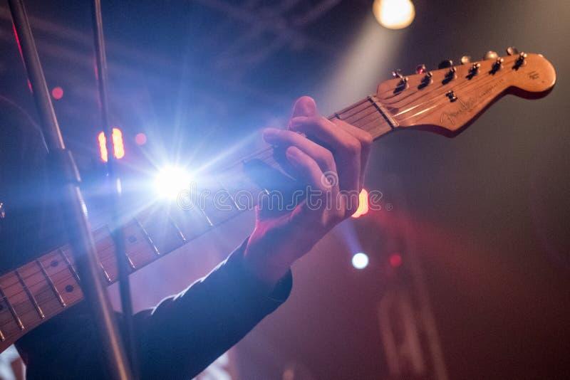 吉他弹奏者在背景中弹在阶段的一把电吉他与光 关闭 库存图片
