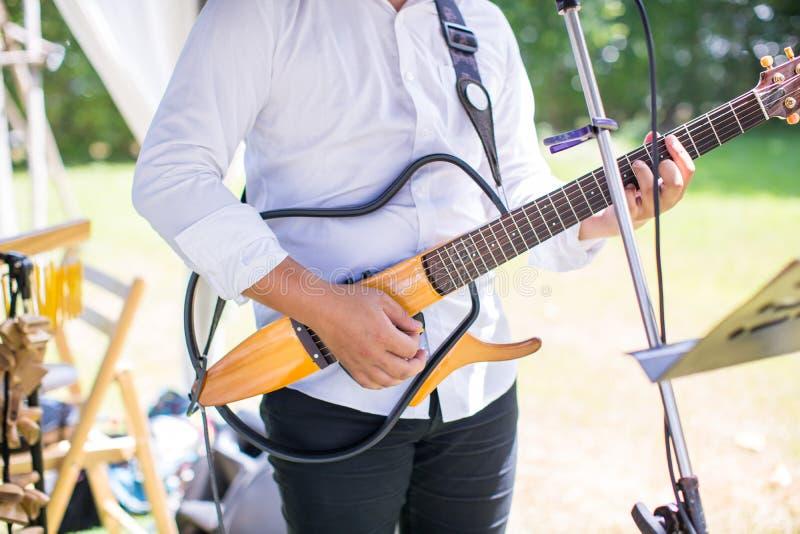 吉他弹奏者戏剧 在一把电吉他的弦 关闭被使用的一把电吉他 免版税库存照片