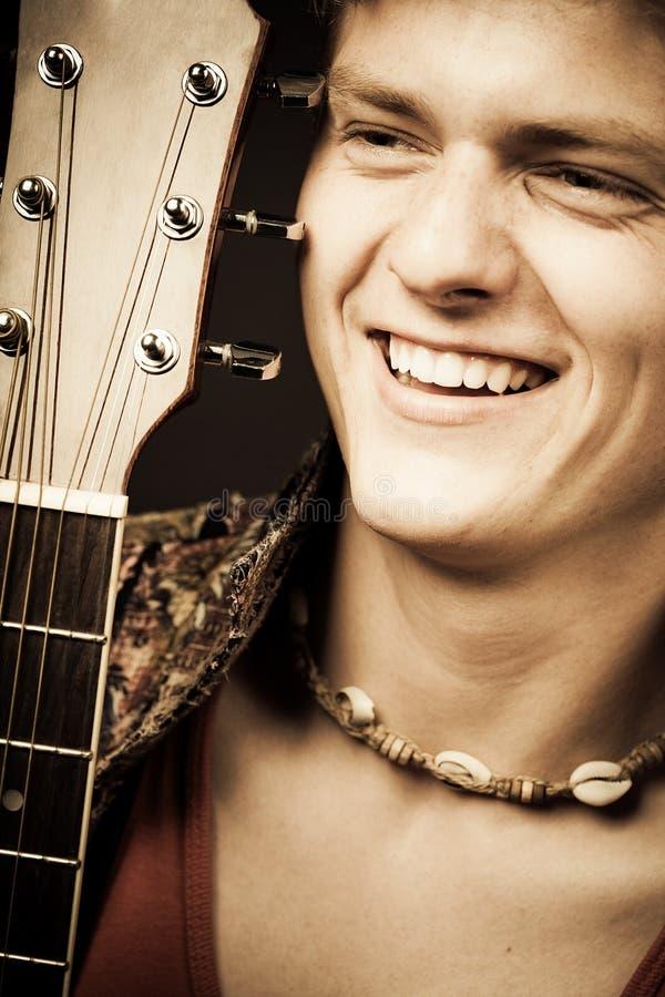 吉他弹奏者笑 免版税库存照片