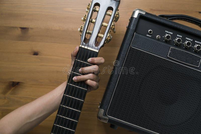 吉他放大器和妇女递拿着在木桌上的一把吉他 免版税库存照片