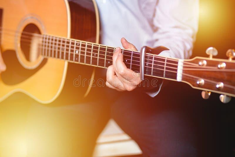 吉他用一个弹在木墙壁背景,电或者声学吉他的人的男性手吉他有自然光的 Concep 库存图片