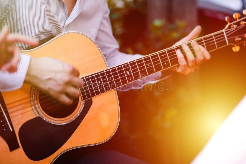 吉他用一个弹在木墙壁背景,电或者声学吉他的人的男性手吉他有自然光的 Concep 库存照片