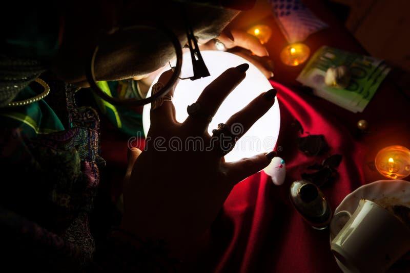 吉普赛妇女算命者在水晶球上把她的手放 免版税库存图片
