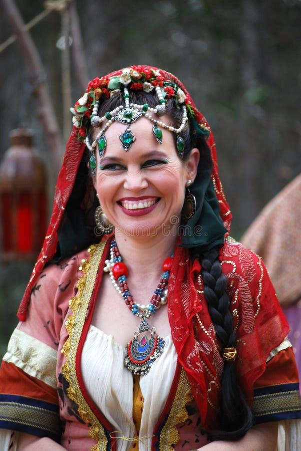 吉普赛服装的微笑的夫人在中世纪市场 图库摄影