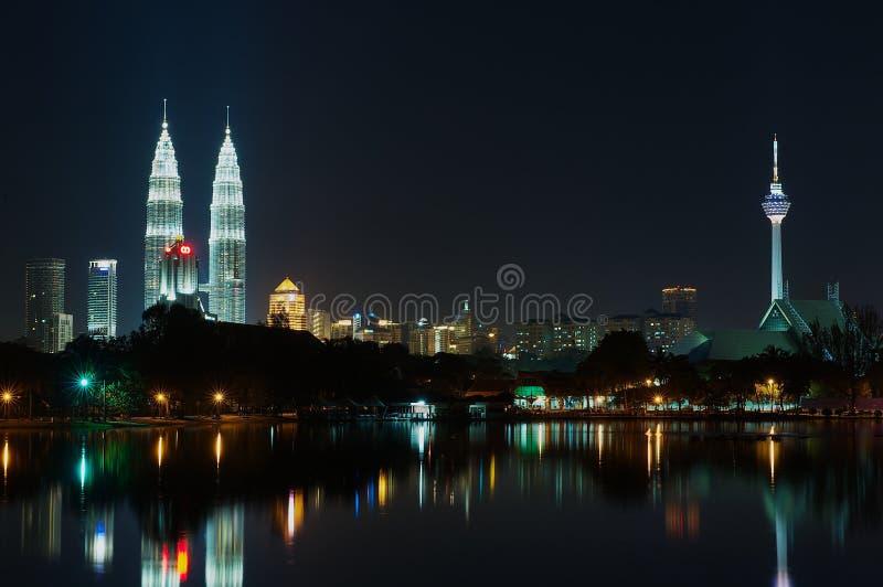 吉隆坡市地平线在与天然碱双塔和反射在池塘的电视塔的晚上在吉隆坡,马来西亚 库存图片