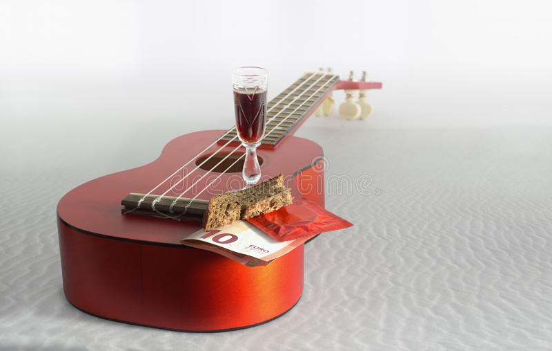 吉他尤克里里琴、面包、欧洲钞票、玻璃与饮料和c 免版税库存照片