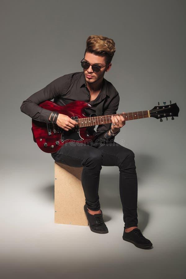 年轻吉他弹奏者坐木箱 免版税库存照片