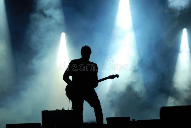 吉他弹奏者现出轮廓在音乐会 库存照片