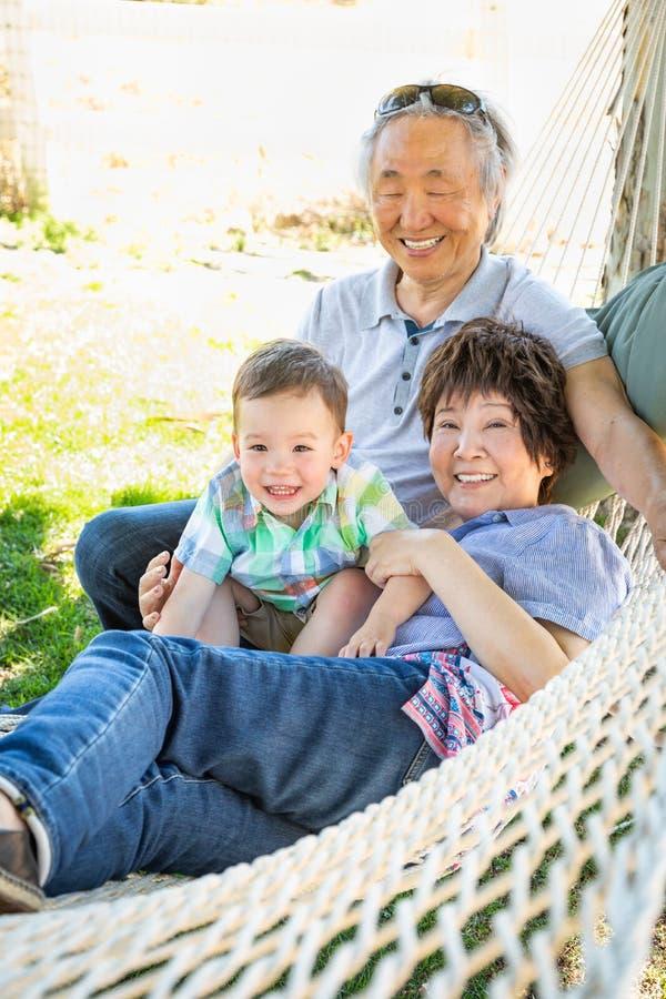 吊床的中国祖父母有混合的族种婴孩的 免版税库存照片