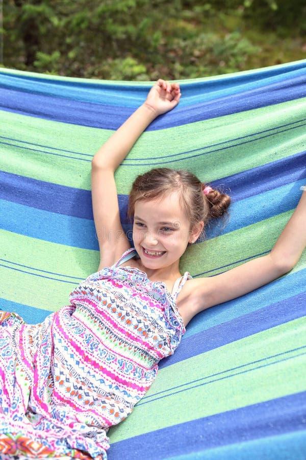 吊床的愉快的笑的女孩 免版税图库摄影