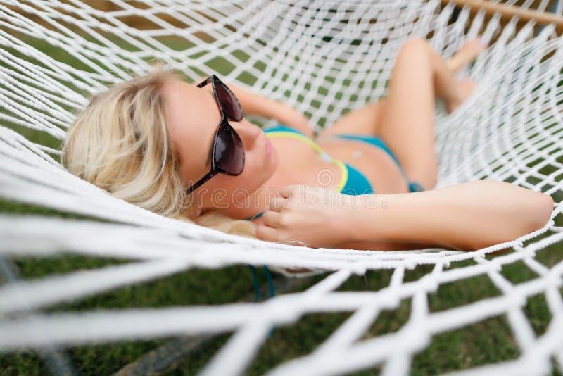 吊床的白肤金发的女孩 免版税库存照片