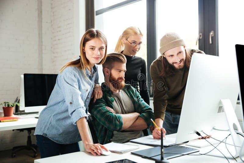 同事在办公室谈话互相使用计算机 库存图片