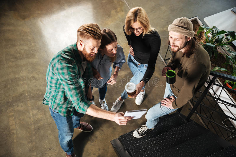 年轻同事在办公室谈话互相拿着笔记本的 免版税图库摄影