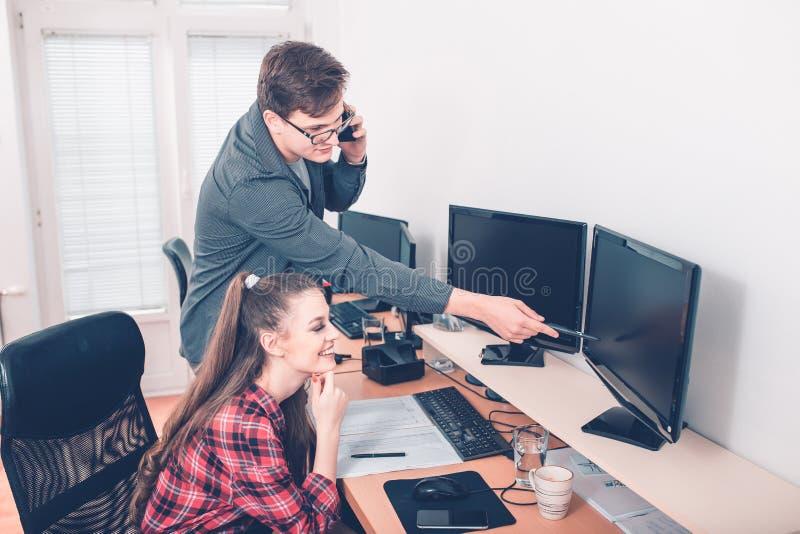 同事在研究台式计算机的办公室 库存照片