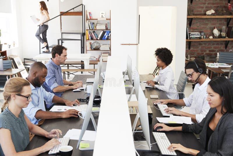 同事坐使用计算机在一个繁忙的开放学制办事处 免版税库存照片