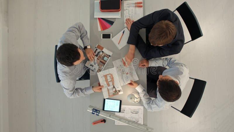 同事室内设计师顶视图谈论数据与黑屏新的现代计算机膝上型计算机和赞成数字式 库存图片