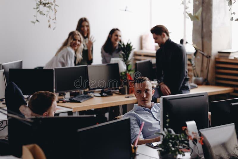 同事年轻队在一个时髦的现代办公室谈论项目 工作过程在办公室 免版税库存图片