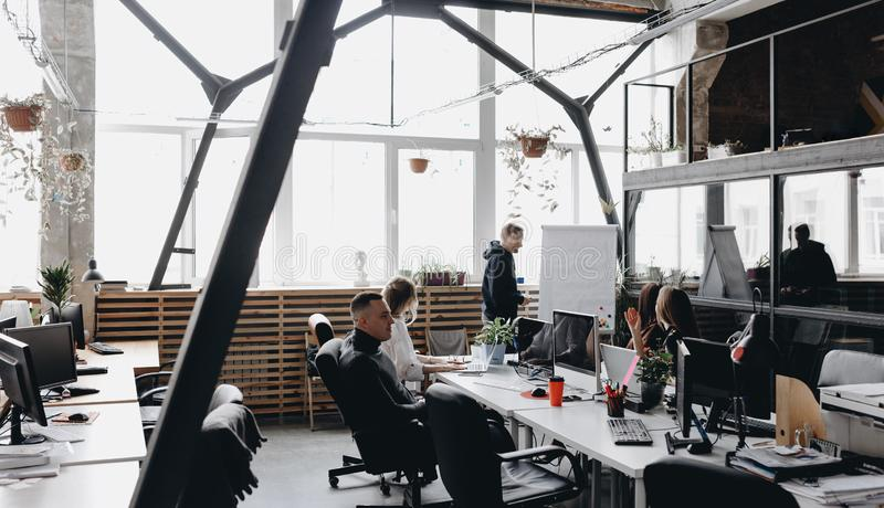 同事的会议 坐在与计算机和膝上型计算机的桌上和听同事的队 免版税图库摄影