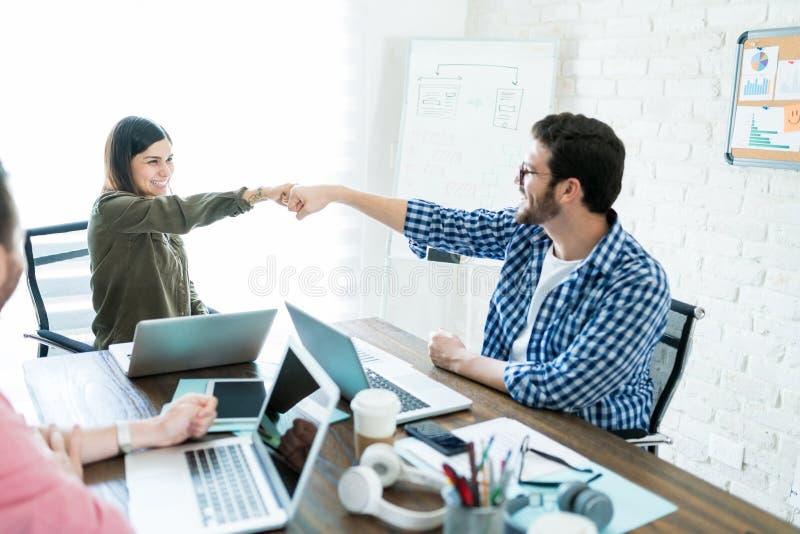 同事结束办公室会议的拳头爆沸 免版税库存照片