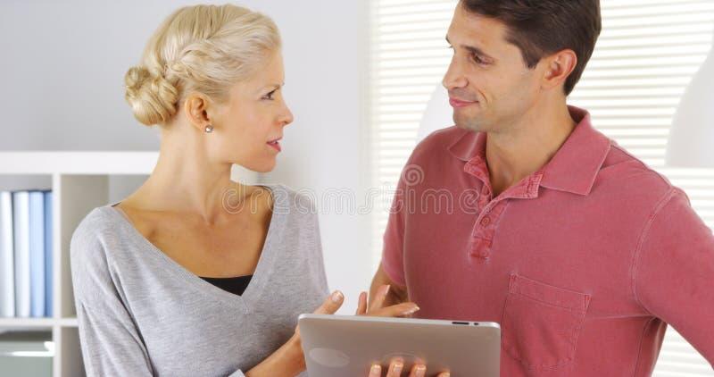 同事谈话与片剂在办公室 免版税库存图片