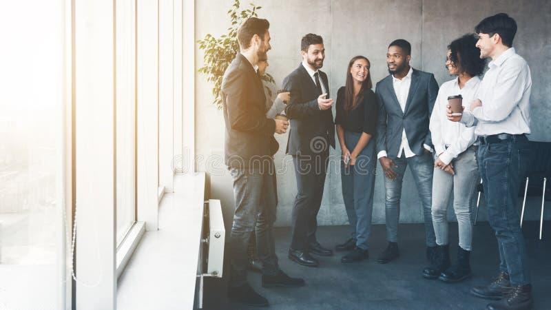同事谈话在咖啡休息靠近窗口 免版税库存图片