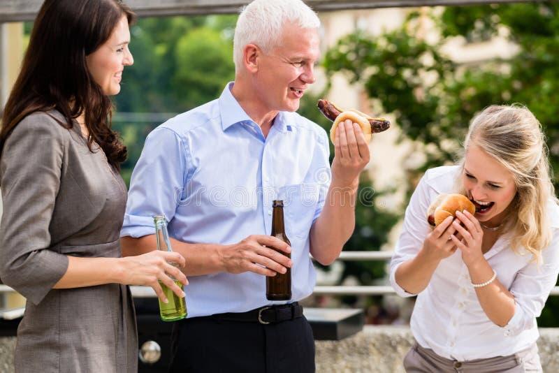 同事饮用香肠和啤酒在工作以后 免版税图库摄影