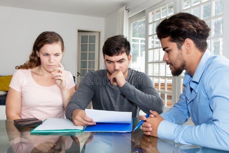 同代理的半信半疑的夫妇读书合同 免版税库存照片