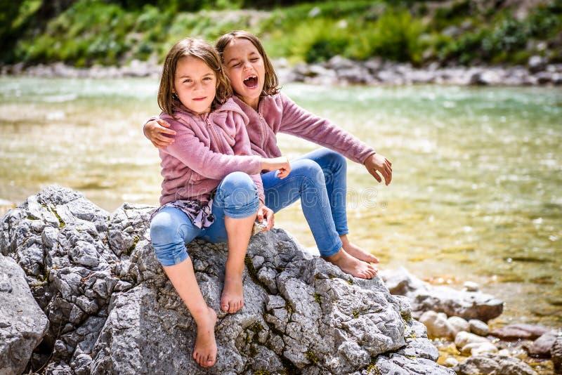 同卵双生女孩坐河岩石在自然暴涨以后 免版税库存照片