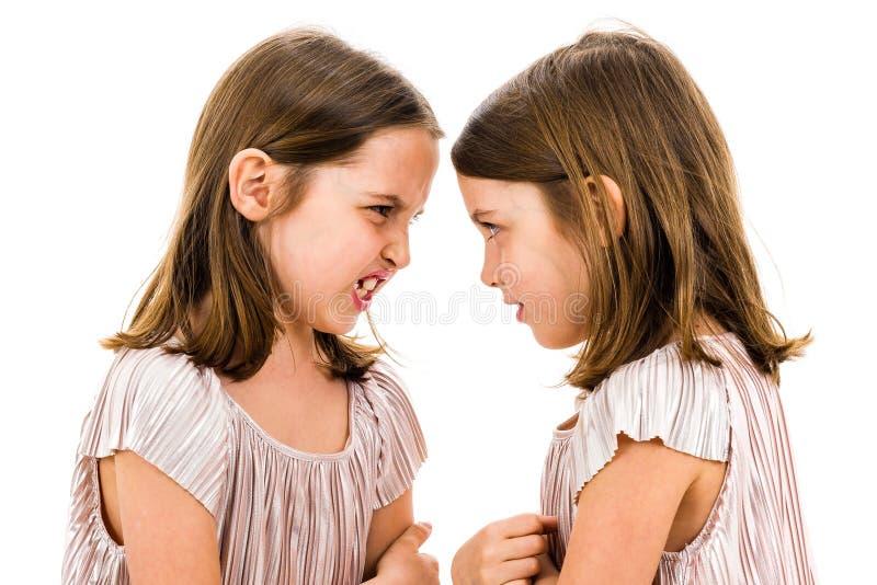 同卵双生女孩姐妹争论叫喊在彼此 免版税图库摄影