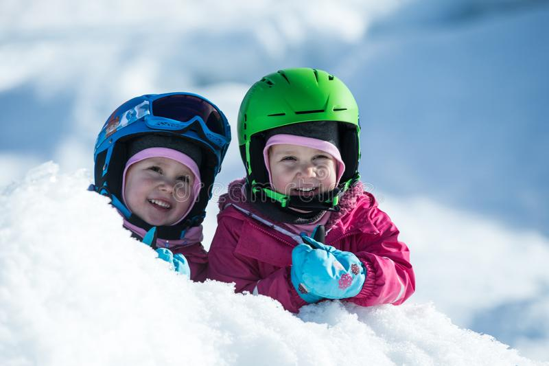同卵双生获得乐趣在雪 与安全帽的孩子 家庭的冬季体育 小孩外面,瑞士阿尔卑斯,山 免版税库存图片