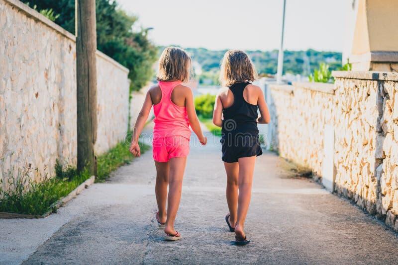 同卵双生走克罗地亚的海岛街道的女孩姐妹 免版税图库摄影