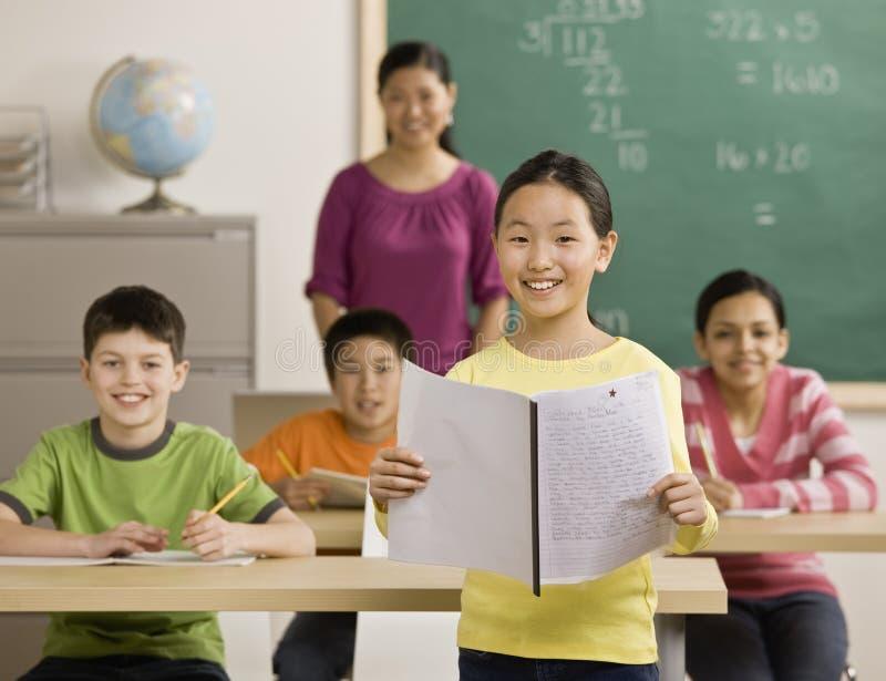 同学女孩读取报表 免版税图库摄影