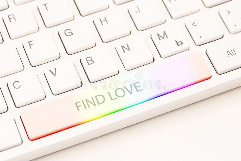 同性恋网上约会的概念 白色键盘以彩虹按钮和题字发现爱 图库摄影