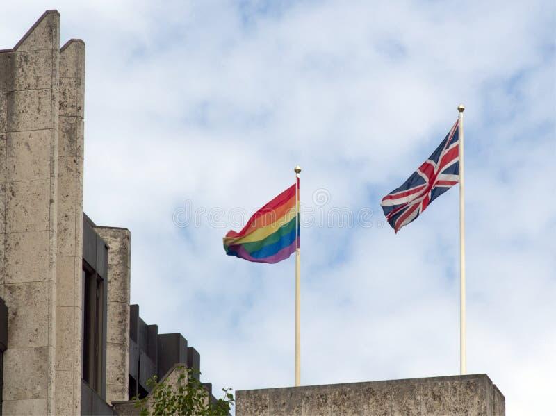 同性恋自豪日旗子和肩并肩英国国旗 图库摄影